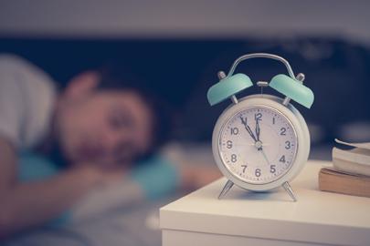 Weniger Schnarchen: Wecker und schlafender Mann