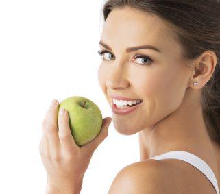 gesundes Zahnfleisch: Frau führt Apfel zum Mund