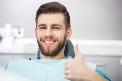 Helle Zähne durch Bleaching und Veneers: Zufriedener Patient auf Behandlungsstuhl