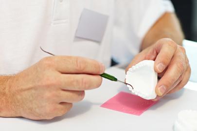 Beispiel für Zahnersatz: Zahntechniker arbeitet an einem Gipsmodell eines Gebisses
