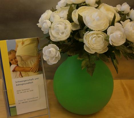 Schwangerschaft Flyer vor Blumenvase